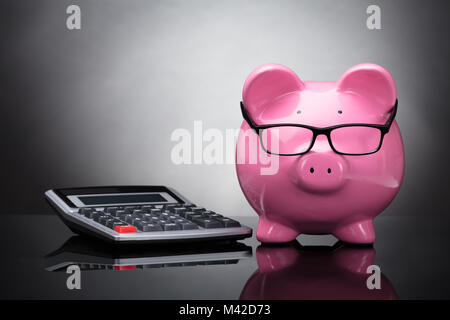 Close-up Of Pink Piggy Bank And Calculator On Grey Background