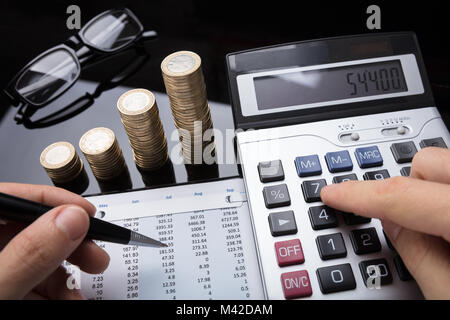 Close-up Of A Businessperson's Hand Calculating Financial Data With Stacked Coins On Desk - Stock Photo