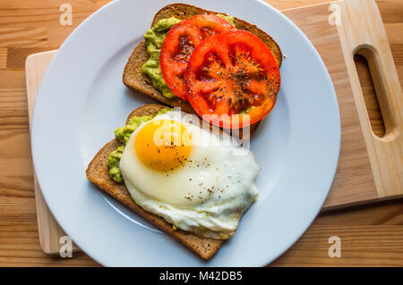 Avocado toast with sliced tomato and a fried egg - Stock Photo