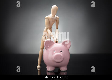 Wooden Dummy Inserting Coin In Pink Piggy Bank On Grey Background - Stock Photo