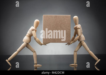 Side View Of Two Wooden Dummy Couple Carrying Cardboard Box On Grey Background - Stock Photo
