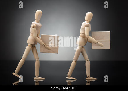 Side View Of Two Wooden Dummies Carrying Square Shaped Blocks On Grey Background - Stock Photo