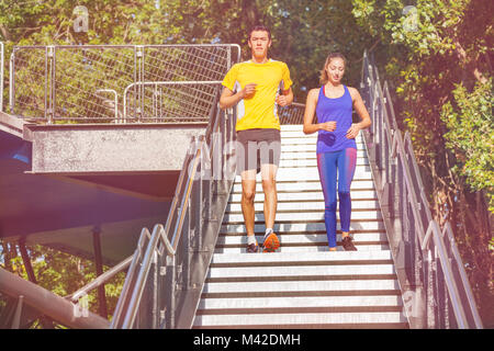 Young athletes running down the steps of city park as part of physical training in summer - Stock Photo