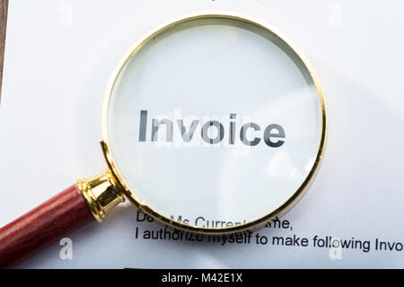 Close-up Of An Invoice Text Seen Through Magnifying Glass - Stock Photo