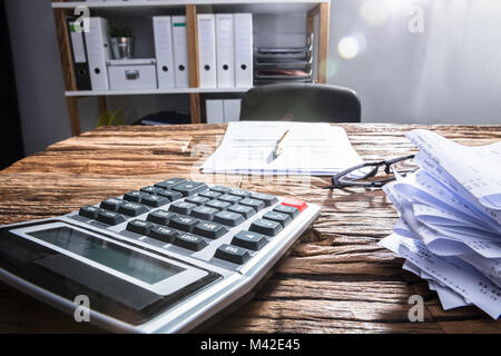 Close-up Of Calculator, Receipts And Invoice On Wooden Desk - Stock Photo