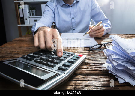 Close-up Of A Businessperson's Hand Calculating Invoice With Calculator At Workplace - Stock Photo