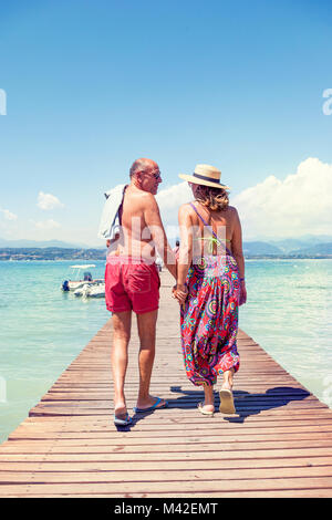 modern mature couple relaxing in swimsuit walking back on the dock of a resort. Concept of beautiful people having - Stock Photo