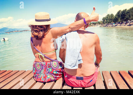 modern mature couple relaxing in swimsuit sitting back on the dock of a resort. Concept of beautiful people having - Stock Photo