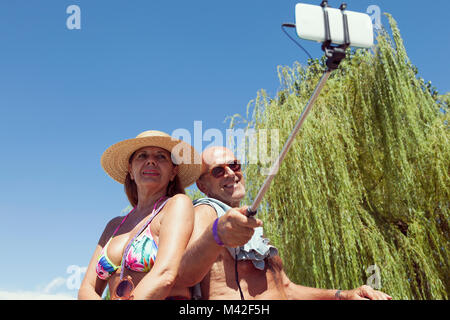 mature couple take a selfie with a smart phone on the beach on vacation. Concept of beautiful people having fun - Stock Photo