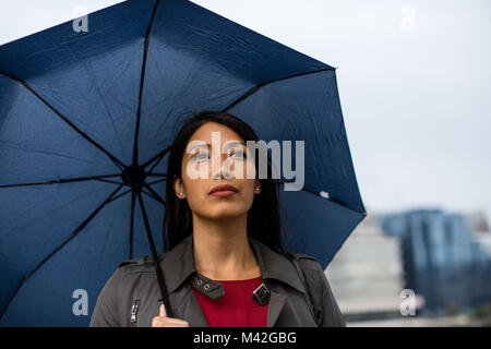 Businesswoman in city holding umbrella in bad weather - Stock Photo