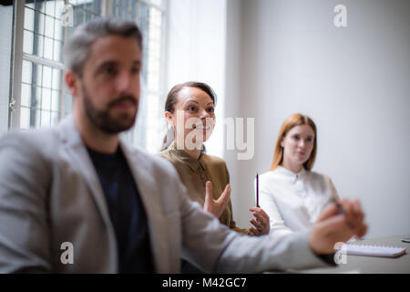 Businesswoman having an idea in a business meeting - Stock Photo