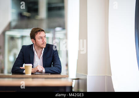 Businessman in a café looking out of the window - Stock Photo