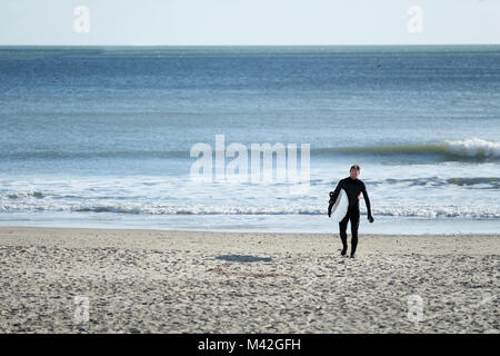 A surfer wearing a full body wet suit walks up the beach, away from the sea, carrying his surf board on a cold bright - Stock Photo
