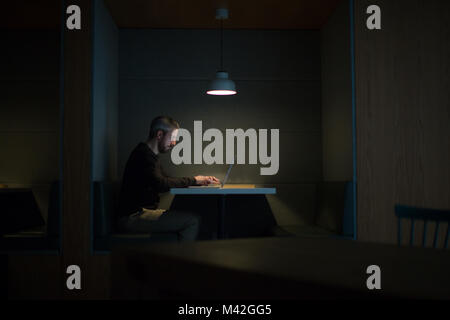 Businessman working late at night in office alone - Stock Photo