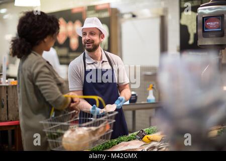 Customer asking fishmonger for advice - Stock Photo