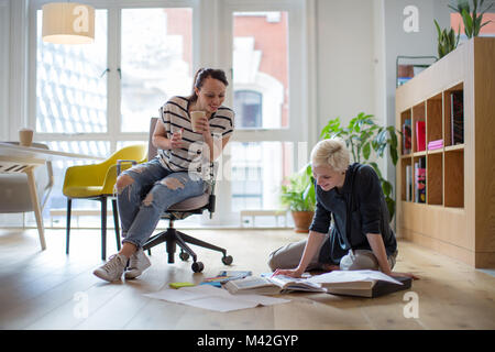 Colleagues discussing ideas with paperwork on office floor - Stock Photo