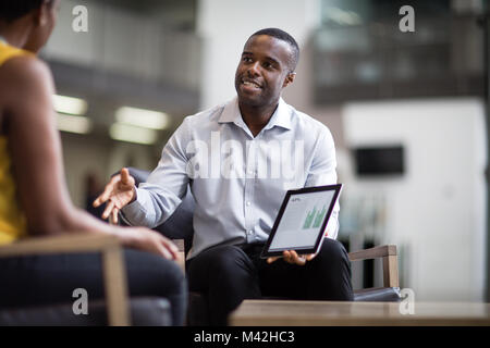 Business meeting in office atrium reception - Stock Photo