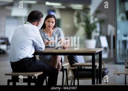 Businesswoman in a meeting using a digital tablet - Stock Photo