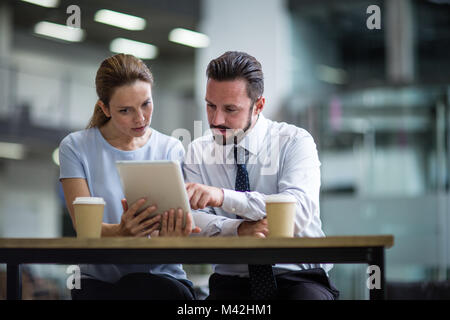 Colleagues using a digital tablet in a meeting - Stock Photo