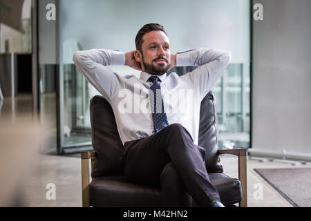 Successful businessman leaning back in chair - Stock Photo