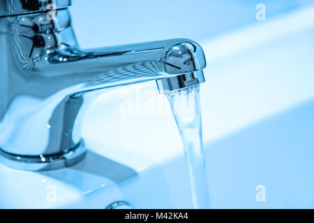 Water running from an open faucet in close-up (blue filter effect). - Stock Photo