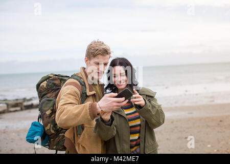 Young couple using smartphone on a winter break at beach - Stock Photo