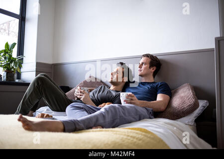 Young male couple relaxing with coffee in bed - Stock Photo