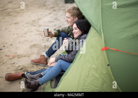 Young couple camping on the beach in fall - Stock Photo