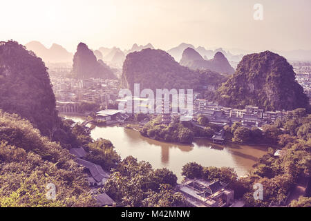 Scenic sunset over Karst mountains formations in Guilin, color toned picture. - Stock Photo