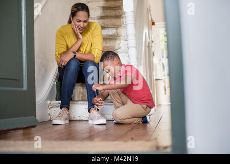 Boy learning to tie shoe laces - Stock Photo