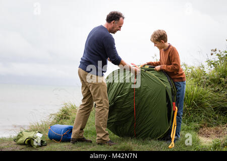 Father and Son putting up a tent together - Stock Photo