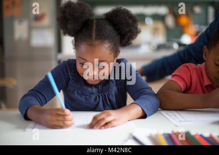 African American girl doing school work at home - Stock Photo
