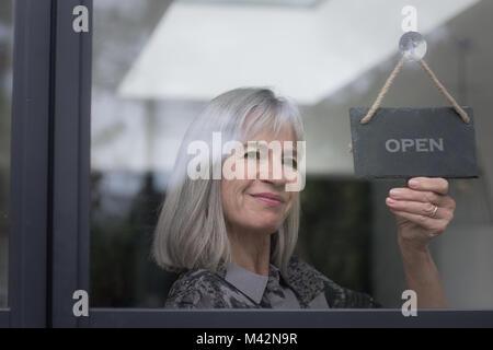 Senior businesswoman opening shop - Stock Photo