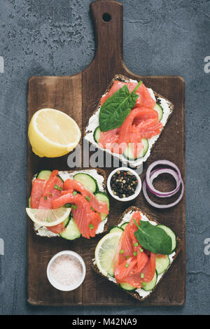 Toast sandwiches with salmon, cucumber and cream cheese on old cutting board. Table top view, toned image - Stock Photo