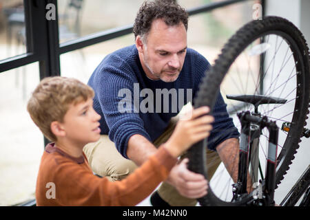 Father teaching Son how to care for his bicycle - Stock Photo