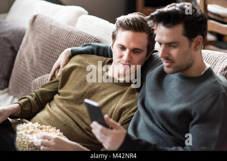 Young male couple relaxing on sofa streaming entertainment - Stock Photo