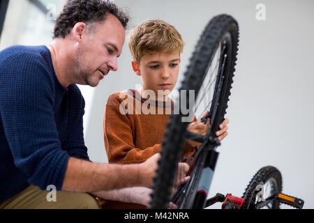 Boy fixing bike with his Dad - Stock Photo