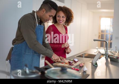 Adult male preparing dinner for girlfriend using digital tablet - Stock Photo