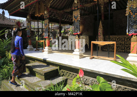 A local girl in traditional dress pray in a Balinese temple.Ubud.Bali.Indonesia - Stock Photo