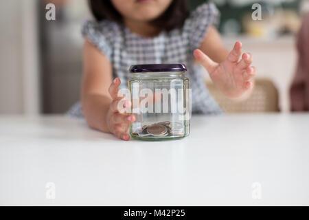 Girl reaching for her pocket money - Stock Photo