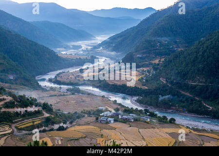Punakha, Bhutan.  Morning Mist in the Mo River Valley. - Stock Photo