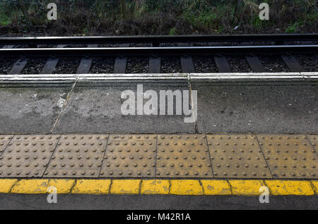 the edge of a platform on a railway or train station with white and yellow lines and textured tactile slabs or flooring - Stock Photo