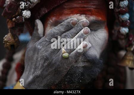 Kathmandu, Nepal. 13th Feb, 2018. A Sadhu or holy man smears ash on his face during Maha Shivaratri festival inside - Stock Photo