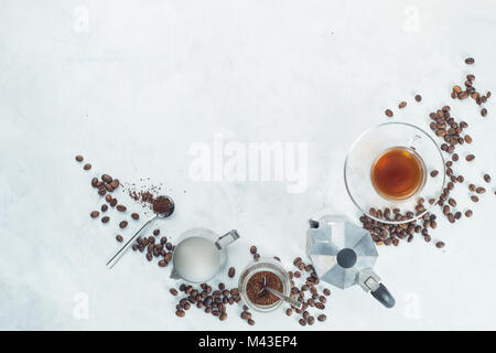Header with brewing coffee ingredients. Moka pot, espresso cup, milk jug, ground coffee jar and coffee beans on - Stock Photo