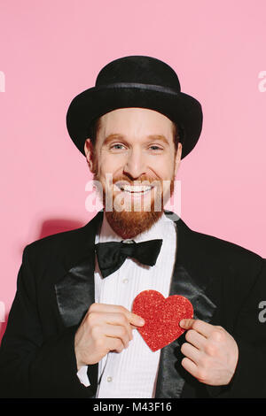 smiling man in tux and top hat holding a red heart on his chest - Stock Photo