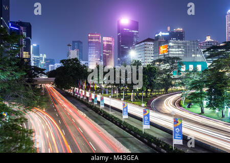 Jakarta, Indonesia - October 27 2017: Traffic, captured with blurred motion as light trails, rush along Sudirman - Stock Photo