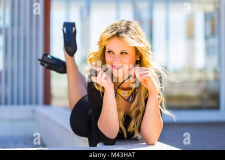 Young woman legs heels lying on her tummy stomach - Stock Photo