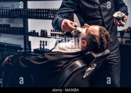 Barber applies shaving foam - Stock Photo