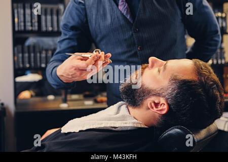 Stylish barber grooming a man's beard in a saloon. - Stock Photo