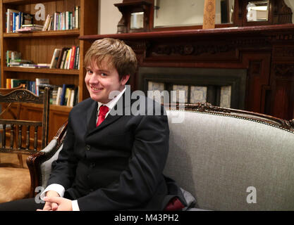 A young man smiling in a suit sat on a sofa taken from the side - Stock Photo